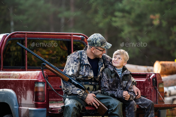 Hunter with his son during the rest sitting inside the pickup truck - Stock Photo - Images