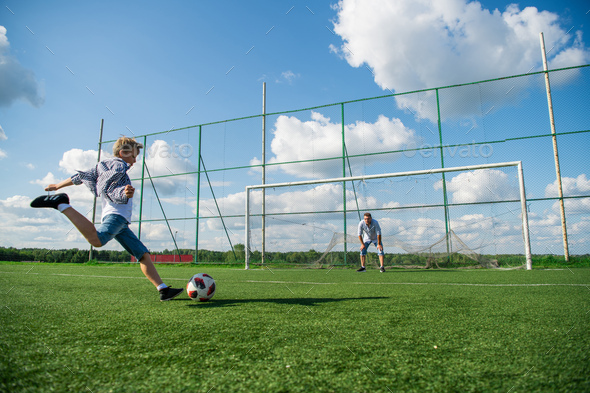 Picture of a boy and his father looks happy while playing football in the field - Stock Photo - Images