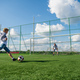Picture of a boy and his father looks happy while playing football in the field - PhotoDune Item for Sale