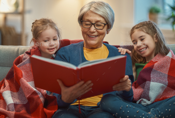 Grandmother reading a book to granddaughters - Stock Photo - Images