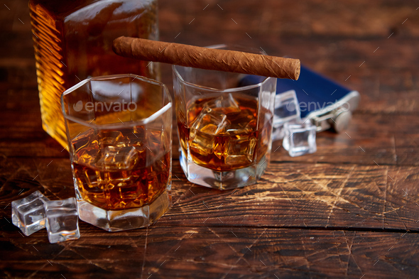 Bottle of whiskey with two glasses and cuban cigar placed on rustic wooden table - Stock Photo - Images