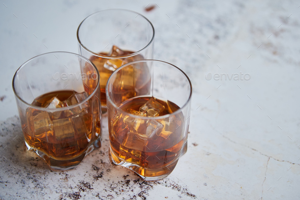 Three glasses filled with ice cubes and old aromatic whiskey - Stock Photo - Images