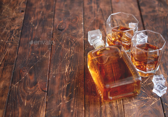 Bottle of whiskey with two glasses placed on rustic wooden table - Stock Photo - Images