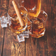 Bottle of whiskey with two glasses and cuban cigar placed on rustic wooden table - PhotoDune Item for Sale