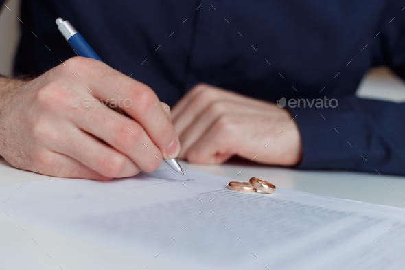 Alone husband signing divorce agreement. - Stock Photo - Images