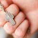 Silver cross in the hand with focus on the cross, shallow DOF - PhotoDune Item for Sale
