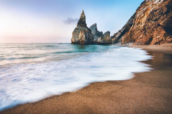 Portugal Ursa Beach. Sea stacks, white ocean wave lit by sunset light - Stock Photo - Images