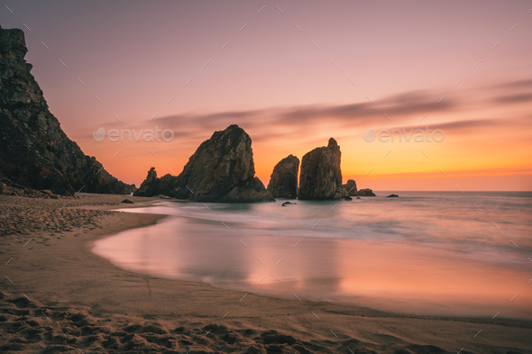 Ursa Beach near Cape Roca at Atlantic Ocean coast in Portugal. Sand beach with sea stacks in evening - Stock Photo - Images