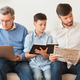Male Family Using Laptop, Reading Book And Newspaper At Home - PhotoDune Item for Sale