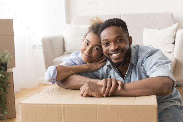 Afro Spouses Embracing Among Unpacked Moving Boxes In New Flat - Stock Photo - Images