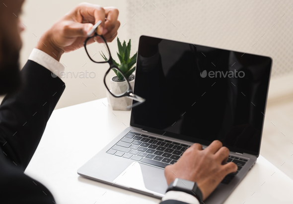Cropped image of businessman using laptop with blank screen - Stock Photo - Images