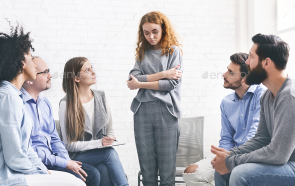 Addicted woman talking talking during rehab group meeting - Stock Photo - Images