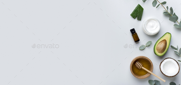 Body cream and avocado half, essential oils and bowl of honey - Stock Photo - Images