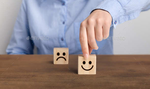 Hand of a businessman chooses a smiley face on wood block cube - Stock Photo - Images