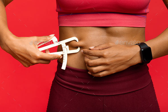 Woman measuring her body fat with body fat caliper - Stock Photo - Images