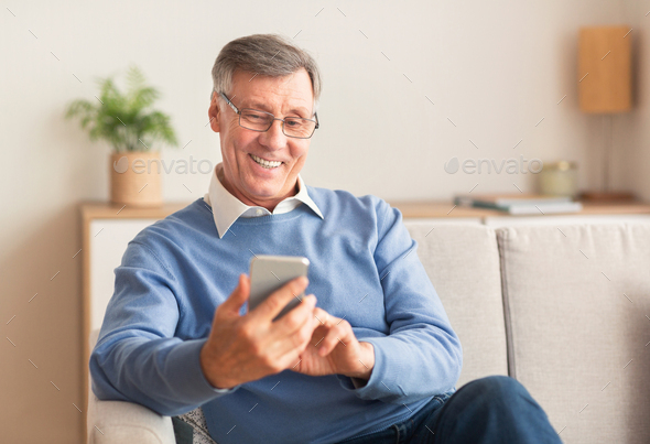 Joyful Elderly Man Using Cellphone Sitting On Sofa At Home - Stock Photo - Images