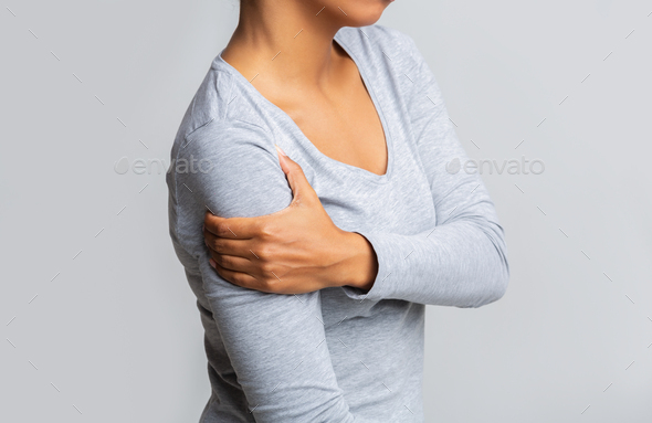 Afro woman holding her forearm over grey background - Stock Photo - Images