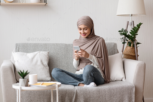 Happy arabic woman in hijab using smartphone on sofa at home - Stock Photo - Images