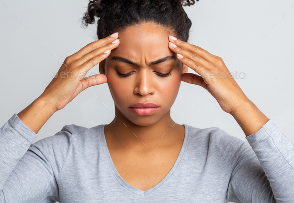 Sad black woman having headache, touching her temples - Stock Photo - Images