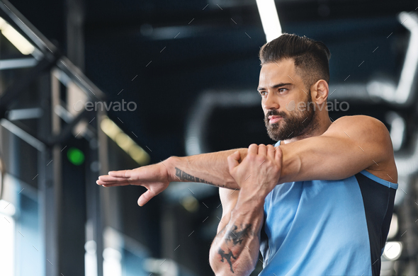 Sportsman stretching his hands before workout training at gym - Stock Photo - Images