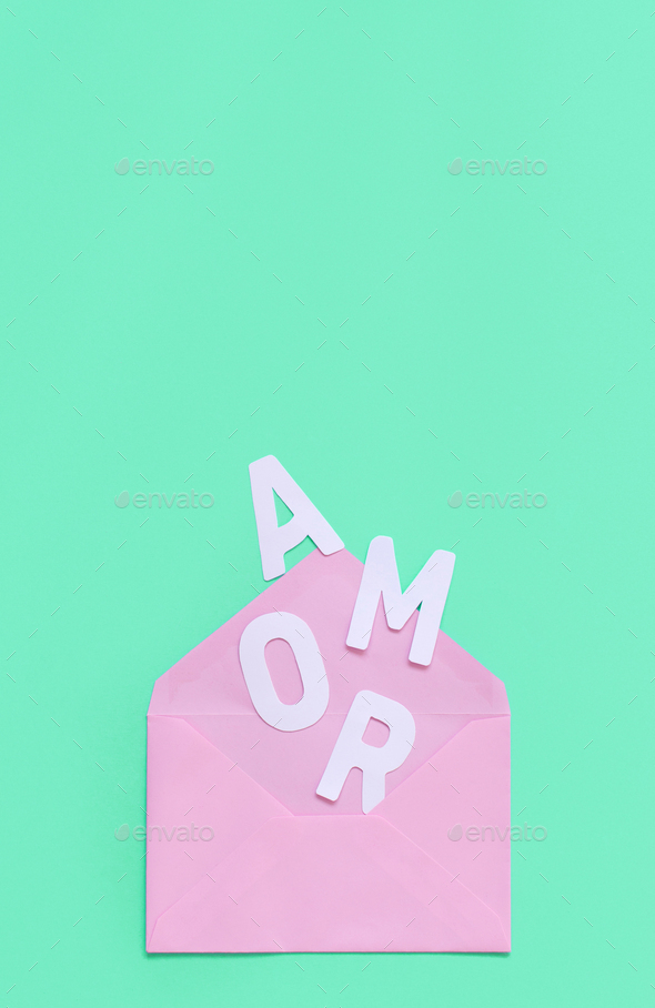Pink envelope and text AMOR on a light green background - Stock Photo - Images