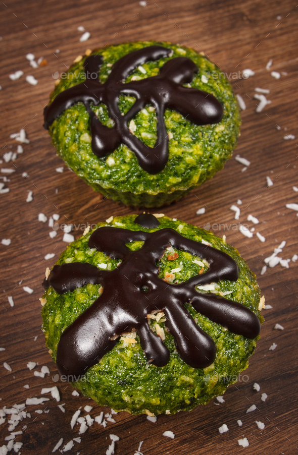 Fresh muffins with spinach, desiccated coconut and chocolate glaze, delicious healthy dessert - Stock Photo - Images