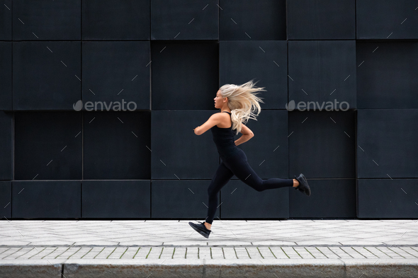 Fit young woman running in minimalist urban city environment - Stock Photo - Images