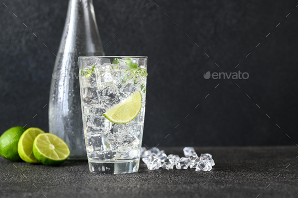 Glass of sparkling water with ice cubes and slice of lime - Stock Photo - Images
