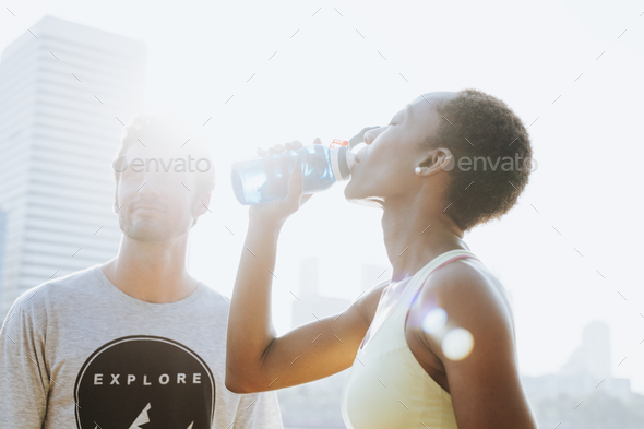 Fitness couple drinking water after workout - Stock Photo - Images