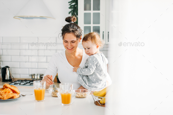 Young woman mom with baby girl on hands cooking breakfast on bright kitchen - Stock Photo - Images