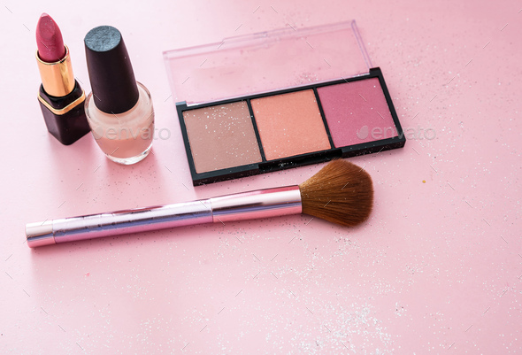 Blush powder and brush, lipstick and nail polish against pink background - Stock Photo - Images