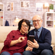 Beautiful elderly couple taking a selfie while sitting on the couch - PhotoDune Item for Sale