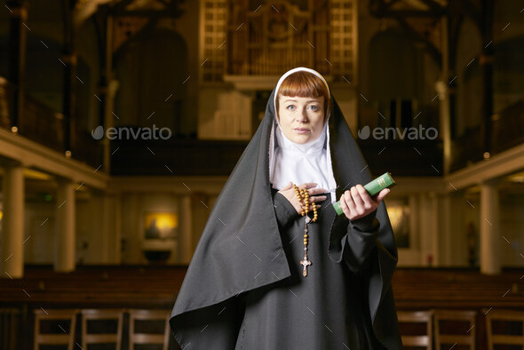 nun in church with rosary and bible - Stock Photo - Images