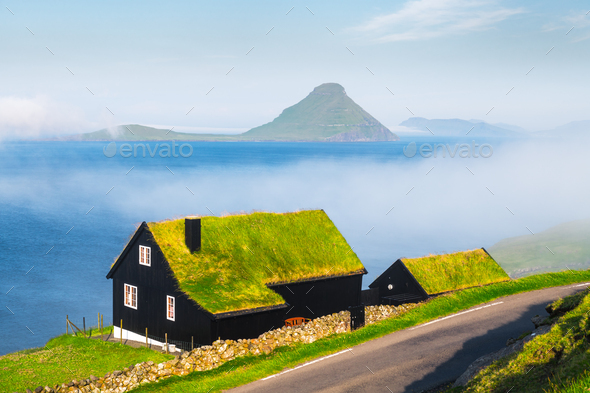 Foggy morning view of a house with typical grass roof - Stock Photo - Images