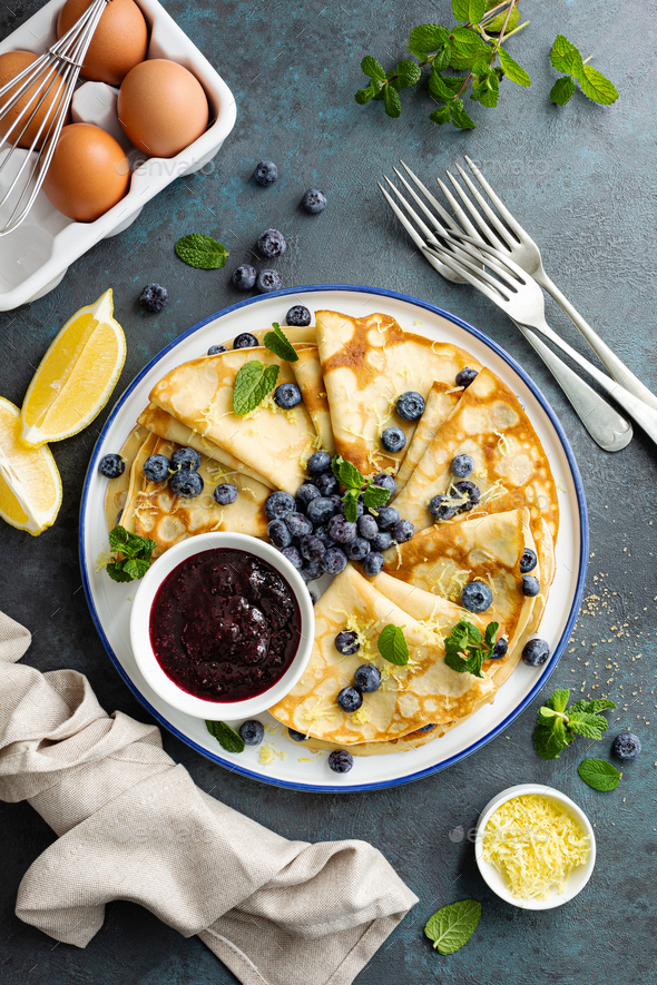 Crepes, thin pancakes with blueberry jam and fresh berries with lemon zest - Stock Photo - Images