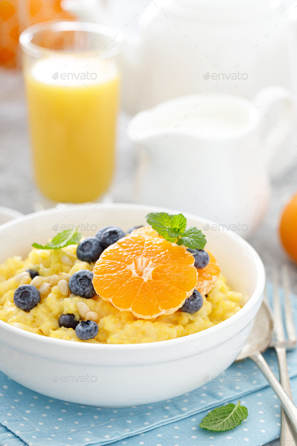 Corn porridge with fresh blueberry, orange and pine nuts in bowl served for breakfast - Stock Photo - Images