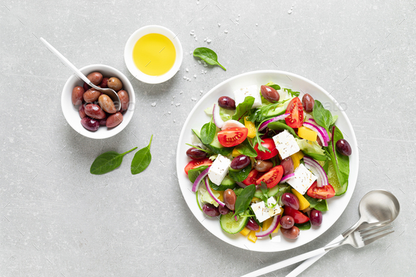 Greek salad with greens, olives and feta chesse on a white plate, top view - Stock Photo - Images