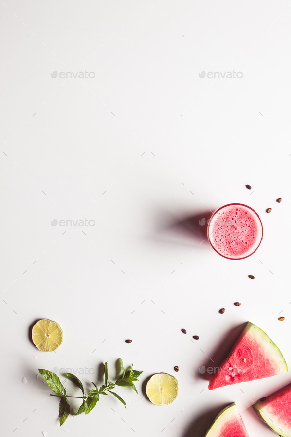 Red slices of ripe watermelon with mint leaves and lime slices on a white background - Stock Photo - Images