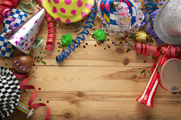 Carnival background on a wooden surface. Masks, hats, coiled streamers, confetti and many more - Stock Photo - Images