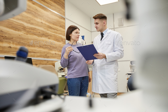 Young WomanTalking to Doctor in Ophthalmology Clinic - Stock Photo - Images