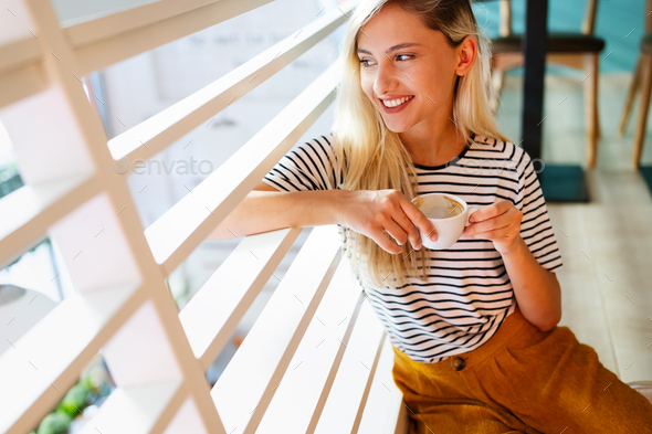 Beautiful woman enjoying a cup of coffee while relaxing at home - Stock Photo - Images