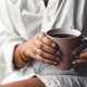 Woman in a white t-shirt holds morning coffee in a pink ceramic cup. Manicure. Front view - PhotoDune Item for Sale