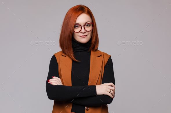 Portrait of smiling red-haired business woman in glasses posing looking at camera - Stock Photo - Images