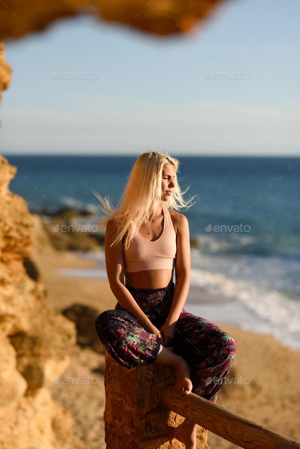 Woman enjoying the sunset on a beautiful beach - Stock Photo - Images