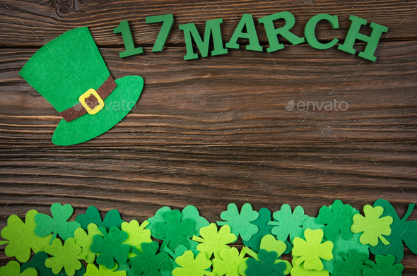 Happy Saint Patrick's mockup of handmade felt hat and shamrock clover leaves on wooden background. - Stock Photo - Images