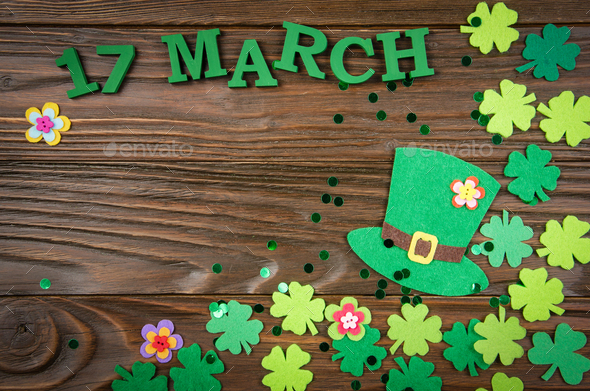 Happy Saint Patrick's mockup of handmade felt hat flowers and shamrock clover leaves on wooden table - Stock Photo - Images