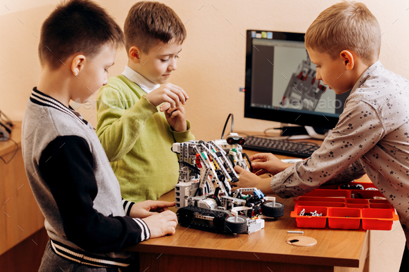 Three smart boys are making robots from the robotic constructor in the School of Robotics - Stock Photo - Images