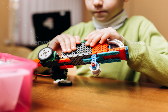 Focused boy dressed in green sweater sits at the table in the robotics school and makes a robot from - Stock Photo - Images
