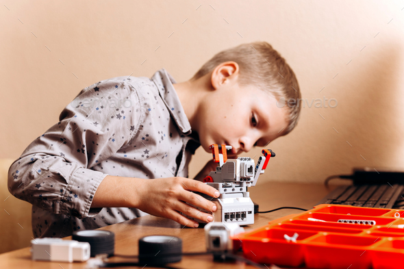 Boy dressed in gray shirt makes a robot from the robotic constructor at the desk in the School of - Stock Photo - Images