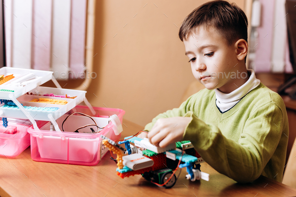 Boy dressed in green sweater sits at the desk with computer and looks at the robot that he made from - Stock Photo - Images